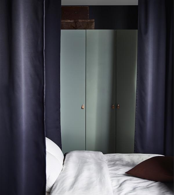 IKEA bietet viele Aufbewahrungselemente für das Schlafzimmer an wie z. B. PAX Kleiderschränke, die es in vielen verschiedenen Stilen, Farben und Größen gibt. Dieser PAX Kleiderschrank mit weißem Korpus hat graugrüne REINSVOLL Türen mit integrierten Stoppern, damit sich die Türen langsam, sanft und l