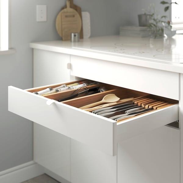 IKEA BILLSBRO white curved handles on a white kitchen drawer.