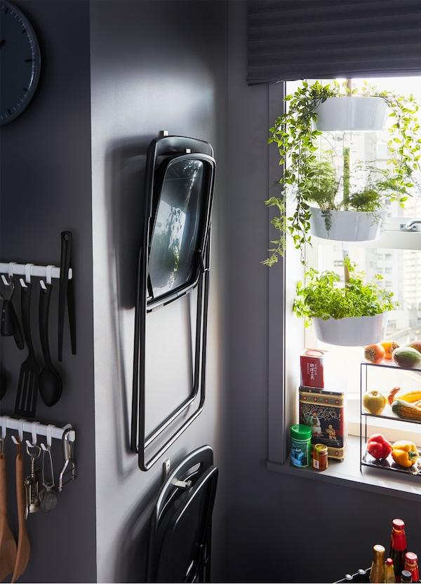IKEA BJÄRNUM aluminium hooks mounted on a wall and holding NISSE black foldable chairs.