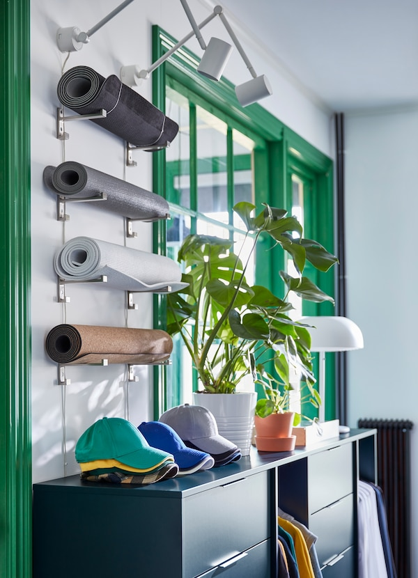 IKEA BJÄRNUM aluminium hooks mounted on the wall to hold yoga mats, skateboards and other items.