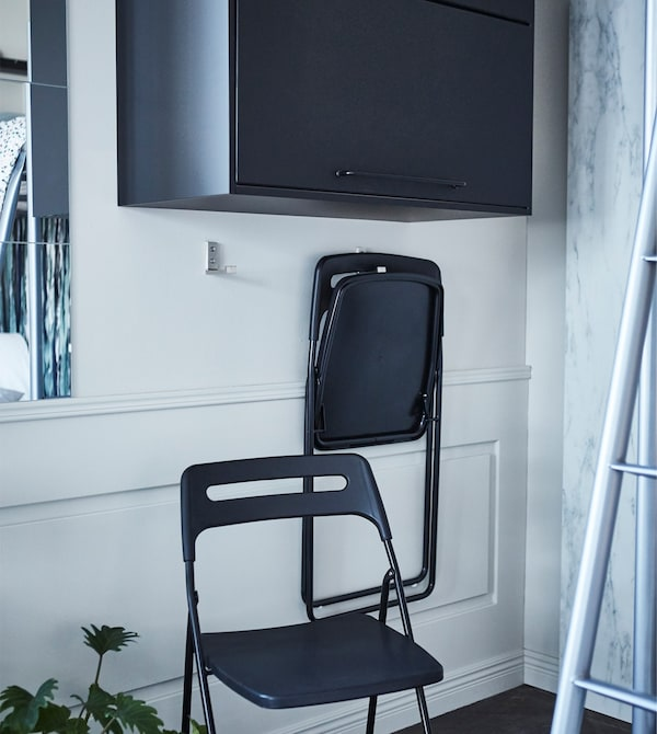 IKEA BJÄRNUM aluminium hooks on a wall used to hang foldable chairs.