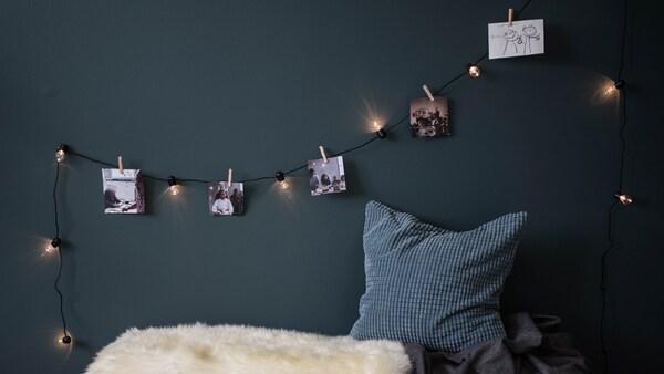 IKEA BLÖTSNÖ ljusslinga som en fotogirlang. Fotografier och teckningar fästa med klädnypor på ljusslinga