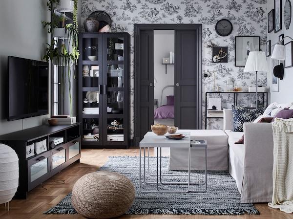 IKEA BRIMNES black tv bench and shelving storage cabinets facing a SANDBACKEN beige sofa in a living room.