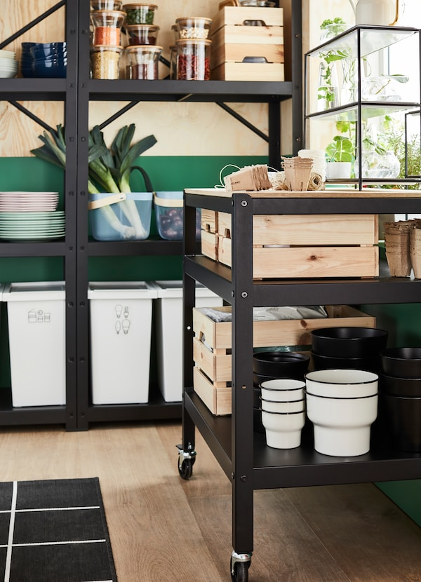 IKEA BROR black trolley is a rollable unit that can store KNAGGLIG pine boxes with fresh produce. SORTERA white plastic waste bins are ideal for trash management, and can be placed on bottom shelves.