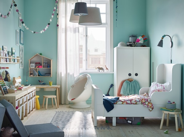IKEA BUSUNGE white extendable bed in a teal wall coloured children's bedroom.