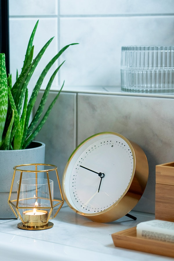 IKEA clock combined with IKEA candle and plant in the bathroom.