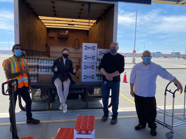 IKEA co-workers and volunteers from Parker Street Food Bank standing beside a truck full of IKEA food products