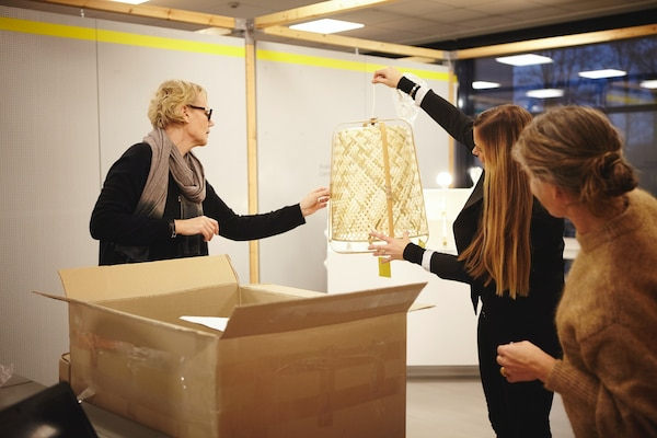 IKEA co-workers looking at KNIXHULT lamp.