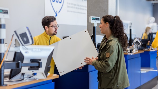 IKEA coworker speaking to a customer by the counter.