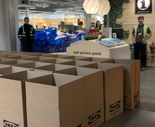 IKEA coworkers with bags of items ready to be packaged inside IKEA boxes to send for donation.