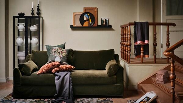 IKEA DEKORERA bildumako hainbat produktu egongela eroso batean daude, kuxinak dituen sofa berde ilunarekin.