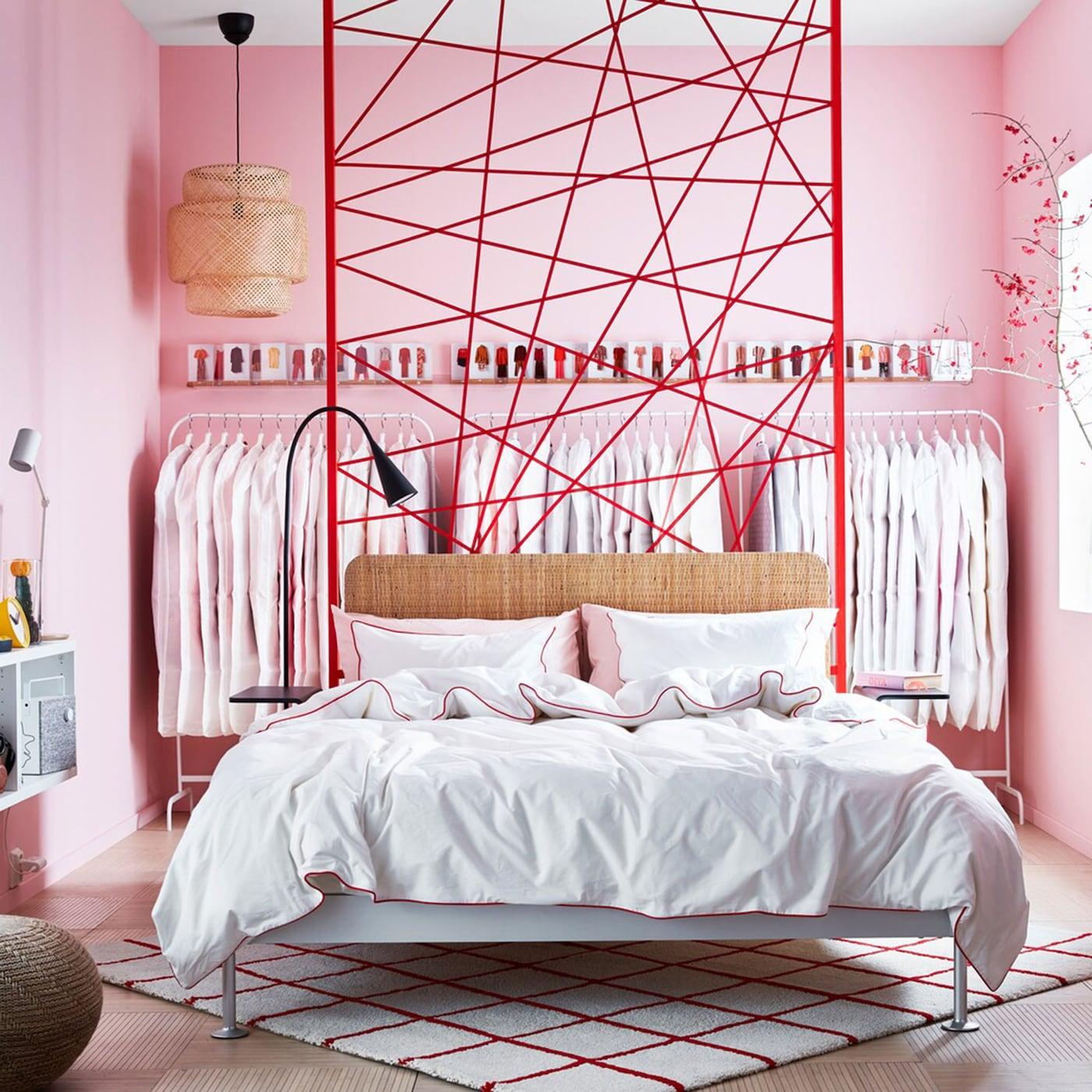 IKEA DELAKTIG bedframe sits in the middle of a pink walled bedroom.