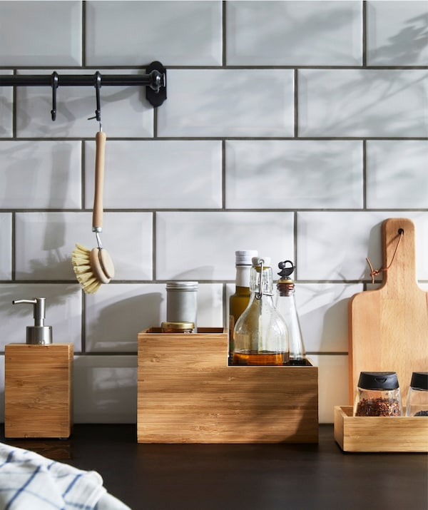 IKEA DRAGAN box in bamboo filled with kitchen countertop items on a kitchen worktop.