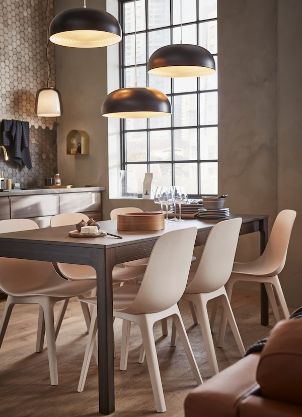 IKEA EKEDALEN dark brown extendable table with six ODGER plastic chairs in beige and white.