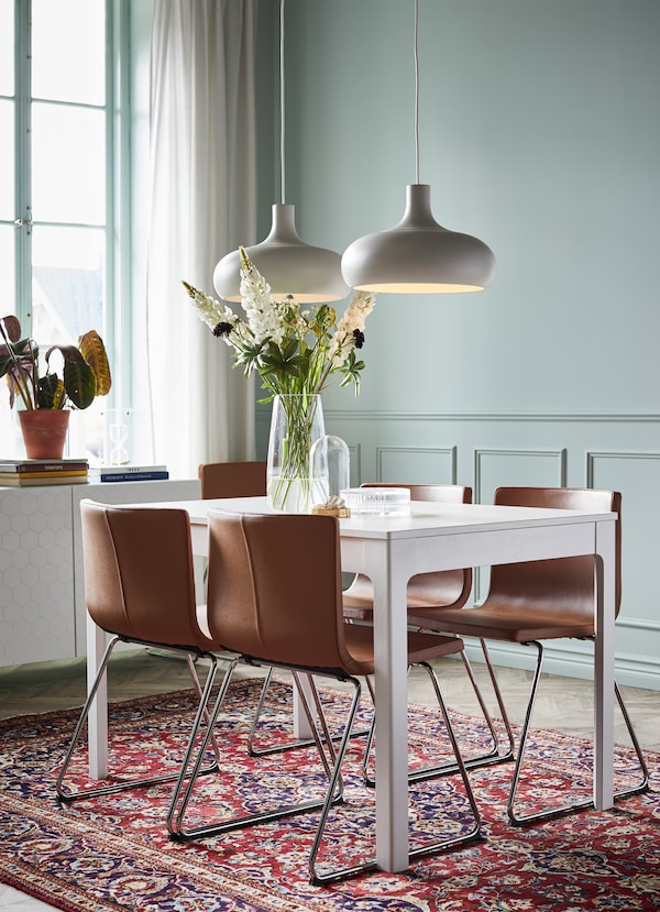 IKEA EKEDALEN white dining table with four brown leather BERNHARD seats.
