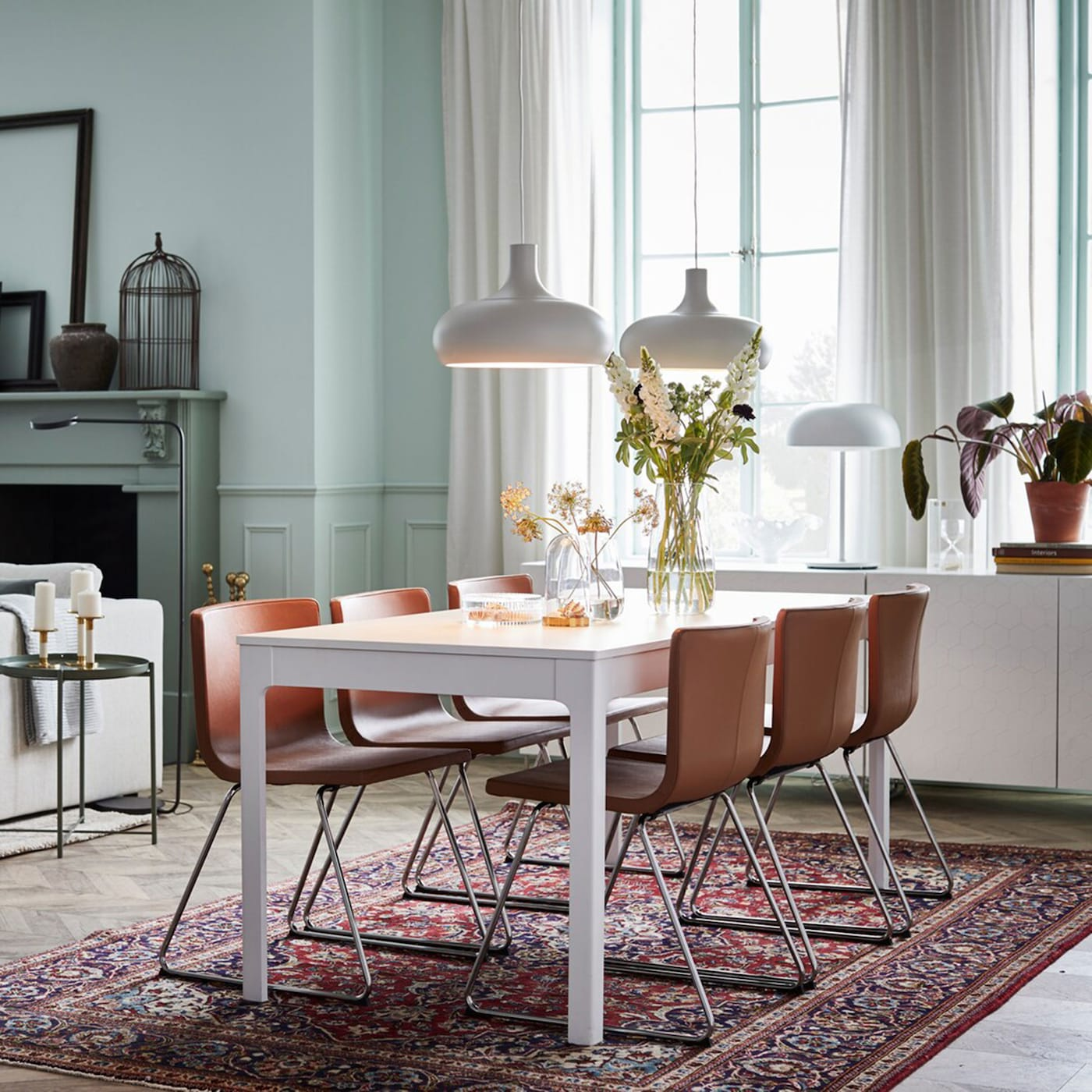 IKEA EKEDALEN white extendable table and BERNHARD brown leather seats in a modern open space dining area.