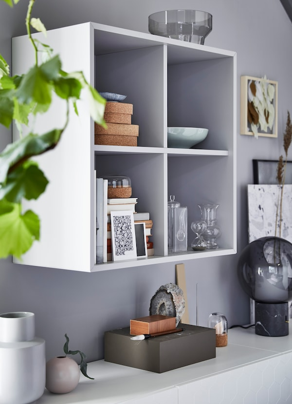 IKEA EKET white wood wall mounted display boxes, with four square shelves, storing acessorie and stacked books inside.