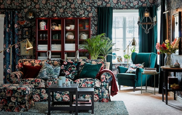 IKEA EKTORP sofa and footstool covered in a vintage flower pattern, furnished in a floral walled living room withdark green colours.