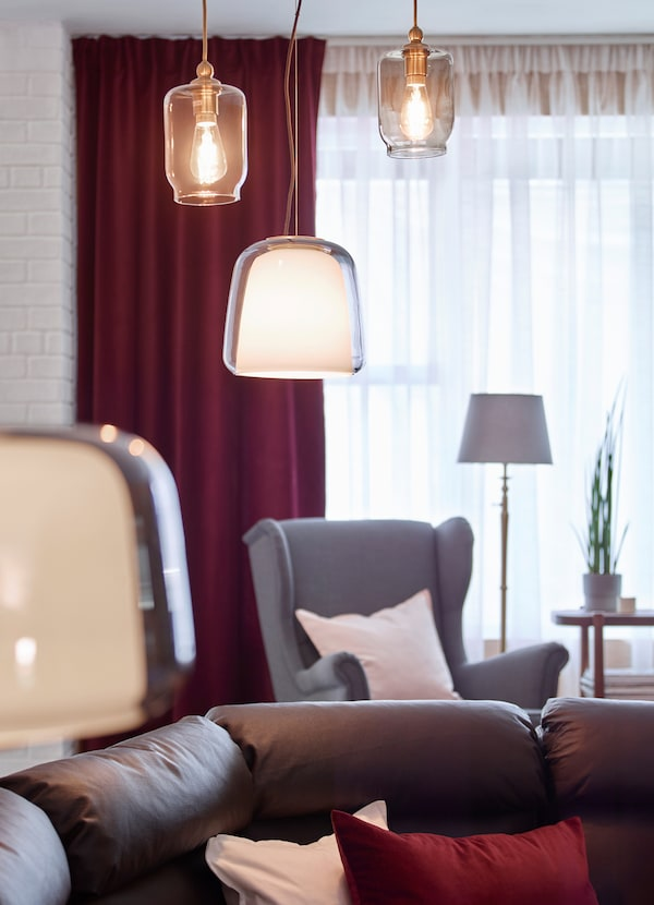 IKEA EVEDAL hanging pendant lamps arranged at different heights above a dark leather brown sofa.