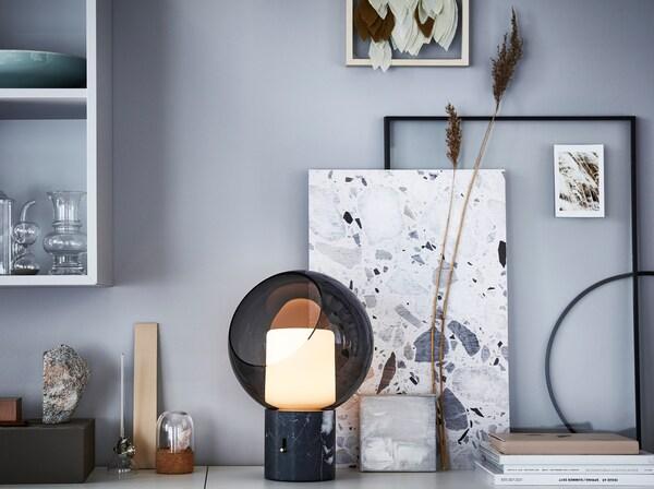 IKEA EVEDAL kerek fekete asztali lámpa, keretekkel és alkotásokkal az asztallapon.