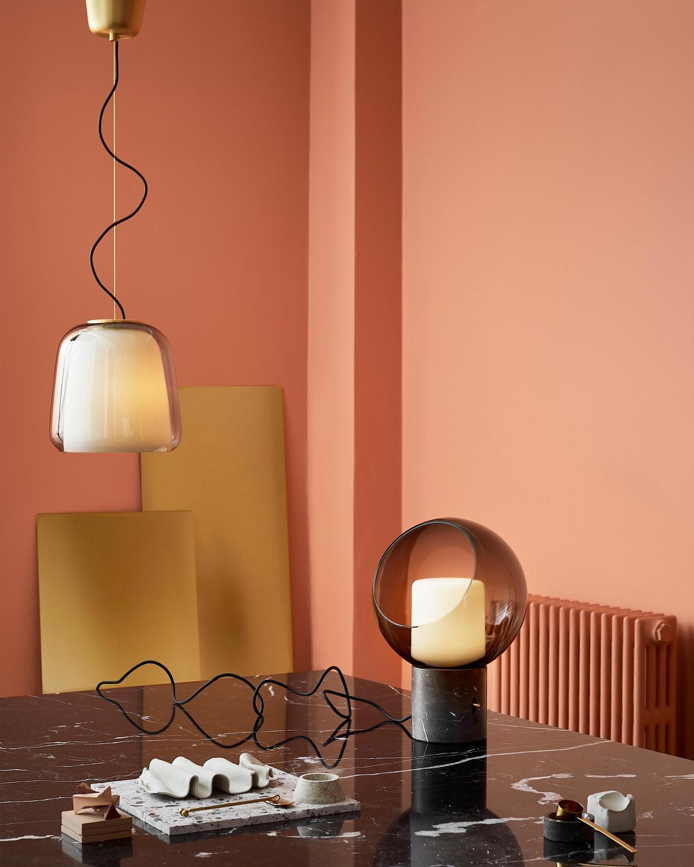 IKEA EVEDAL -pöytävalaisin on pallonmuotoinen lasivalaisin, jossa on messinginvärinen himmennin. Siinä on myös marmorijalusta.