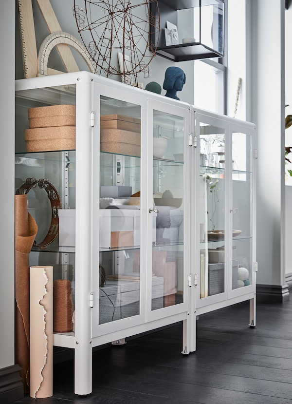 IKEA FABRIKÖR white drawer storage cabinet with clear glass doors, showing off trinkets and boxes inside.