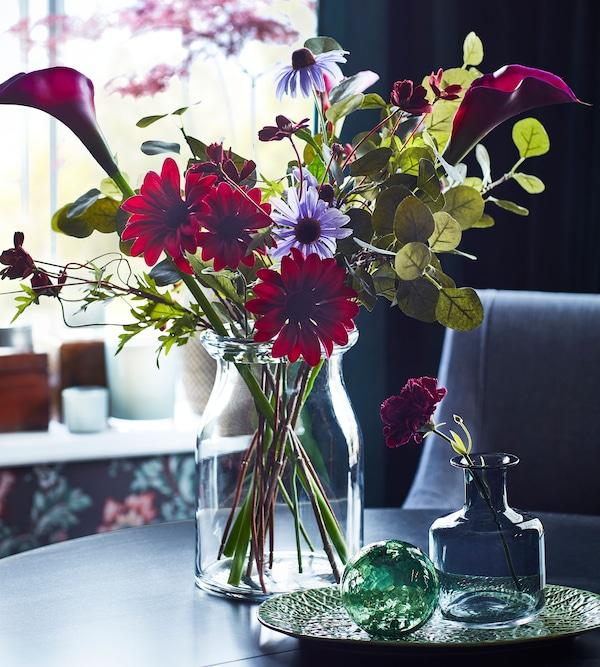 IKEA FEJKA ІКЕА ФЕЙКА червоні та фіолетові штучні квіти в BEGÄRLIG БЕГЕРЛІГ скляній вазі.