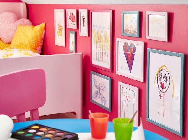 IKEA FISKBO fibreboard frames in blue and pink showcasing children's drawings.
