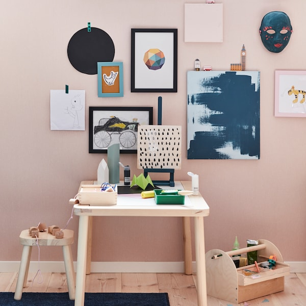 IKEA FISKBO pink and black picture frames displaying children's artwork and graphic prints.