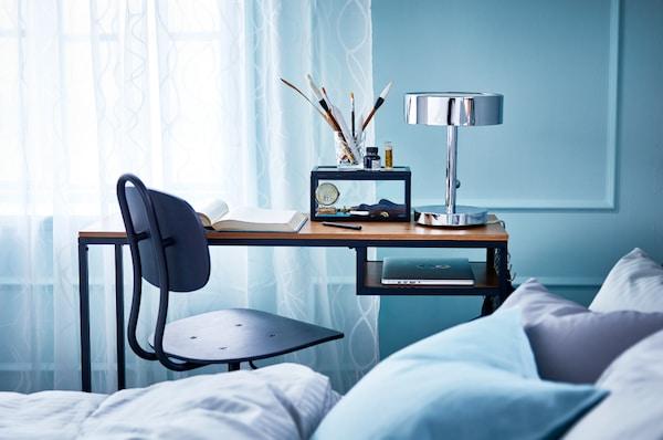 IKEA FJÄLLBO Mesa p/portátil num quarto azul, com uma cadeira preta em estilo industrial. Em cima da secretária um candeeiro de mesa STOCKHOLM, pincéis, um livro e em baixo, arrumado um computador portátil.
