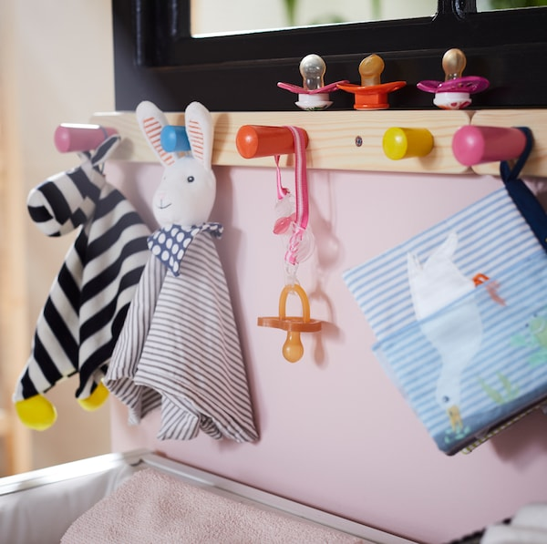 IKEA FLISAT pine rack with 4 colourful knobs in pink, blue, yellow and orange holding pacifiers and baby toys.