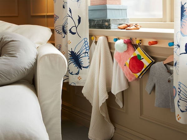 IKEA FLISAT šipka sa 4 šarene kvačice ispod prozorske daske s plišanim igračkama i dječjim ručnicima.