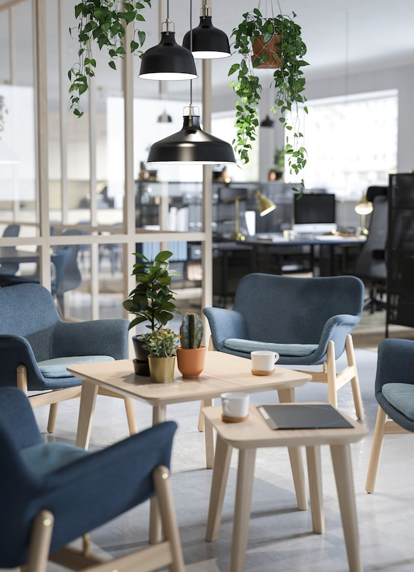 IKEA FOTO pendant lamps, hanging plants and VEDBO sloped blue chairs in a waiting area.