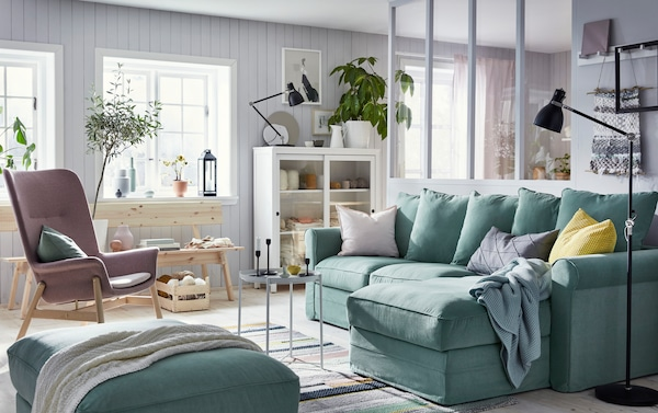 IKEA GRÖNLID green sofa with storage, HEMNES white stained wood storage unit with glass doors, and INDUSTRIELL natural untreated pine bench in a calm living room setting.