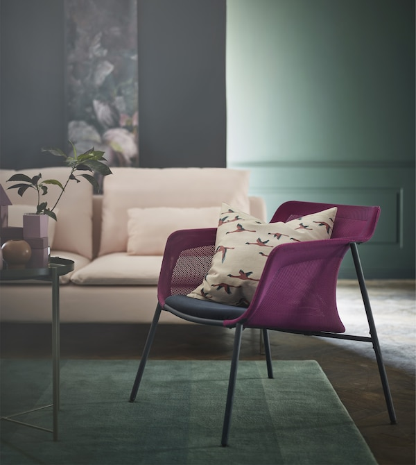 IKEA has a variety of pink and green decor for your living room like rugs, sofas, vases and cushions. IKEA PS 2017 armchair is lightweight and modern with a woven mesh pink shell and a blue seat.