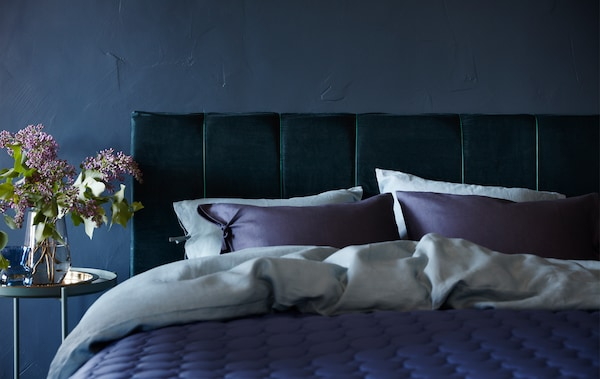 IKEA has tips for an upholstered headboard how to like this one made from dark blue cotton velvet curtains, foam padding and a MALM bed frame.