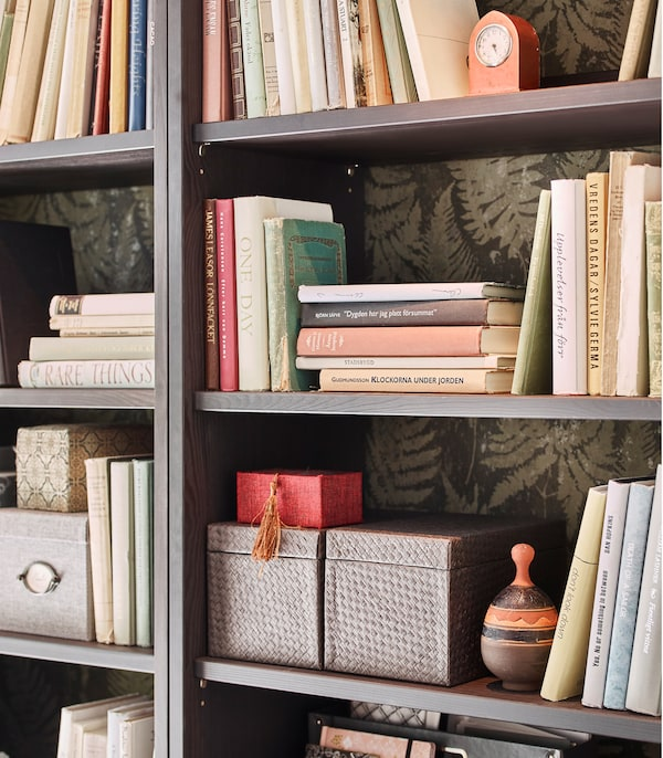 IKEA HAVSTA dark brown storage cabinets with four open shelves, letting the leafy wallpaper of the room peek out from the books and boxes stored on the shelves.