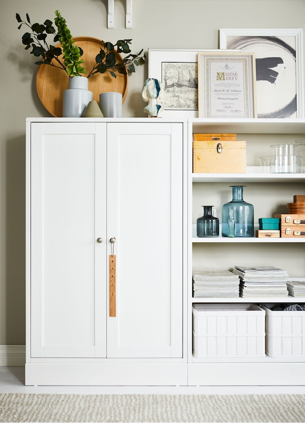 IKEA HAVSTA white cabinet, with plinth, beside open storage, with plants, pots, pictures, baskets and decorative accessories.