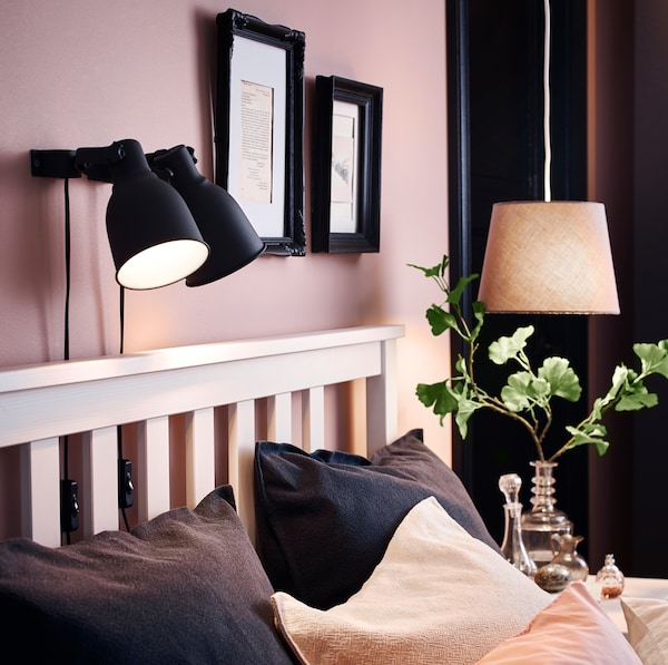 IKEA HEKTAR black mounted lamplights above a white HEMNES bedframe, turned on to emit a warm glow.