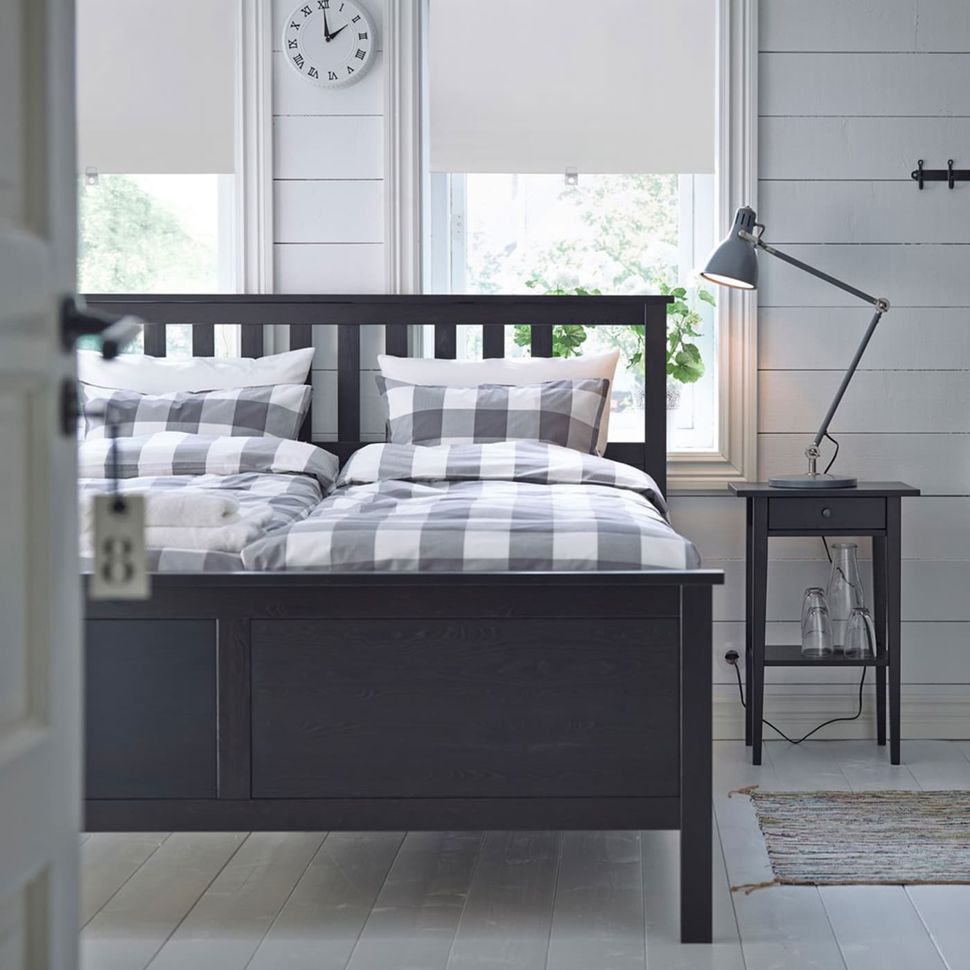 IKEA HEMNES black brown bedframe furnished with light grey and white checkered bedsheets in a small bedroom.
