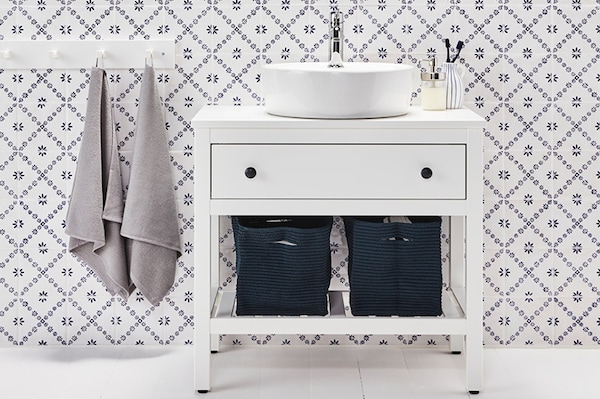 IKEA HEMNES/RÄTTVIKEN bathroom vanity, mirror cabinet, and bathtub in a blue and white bathroom.