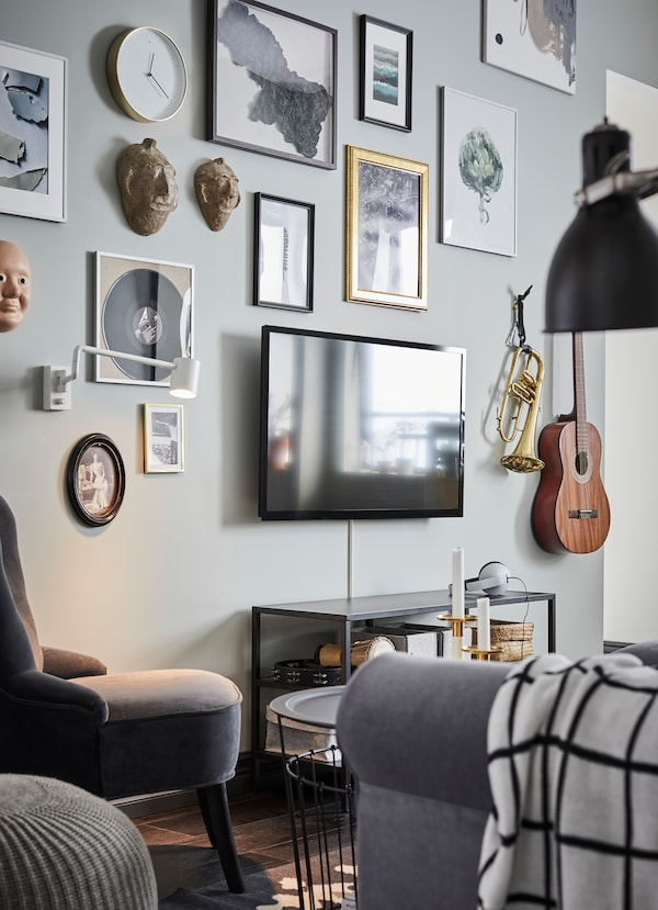 IKEA HOVSTA black picture frames and mounted musical instruments arranged around a TV.