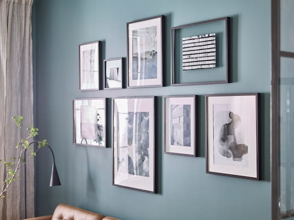 IKEA HOVSTA plastic black picture frames in different shape and sizes, arranged on a wall.