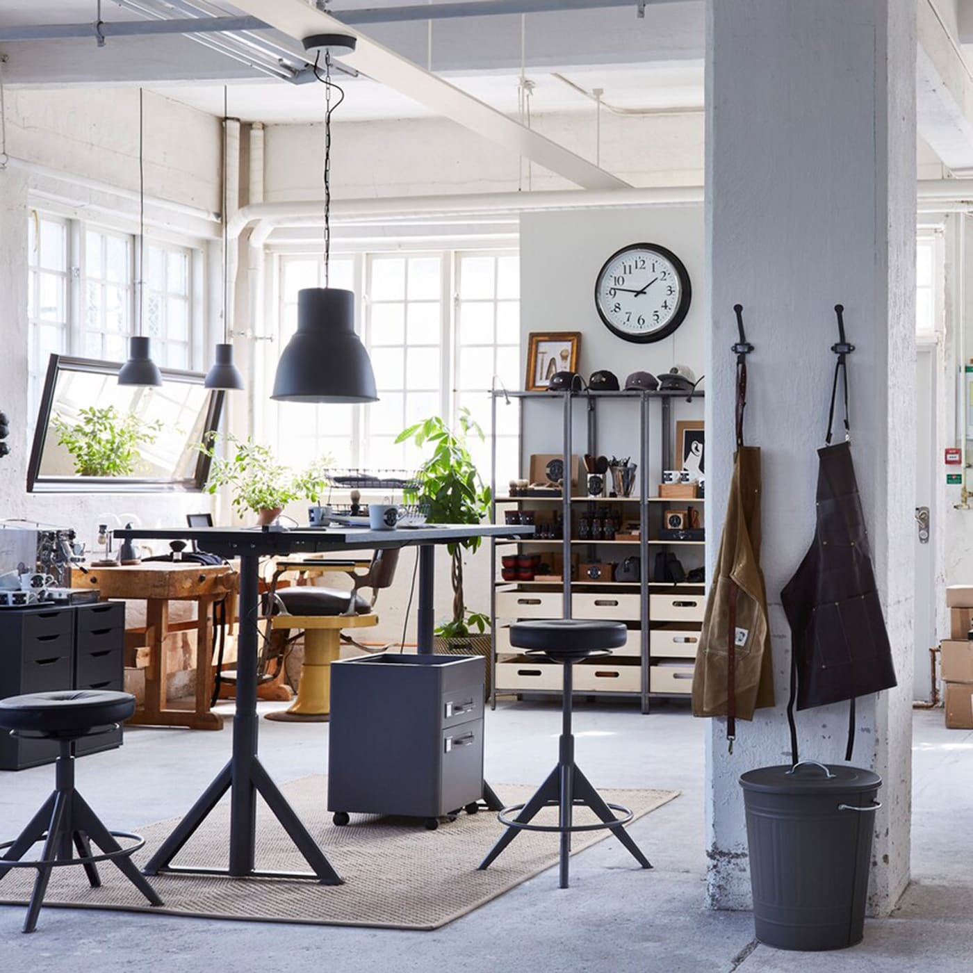 IKEA IDÅSEN office furniture is flexible for big businesses to small startups like this one in an industrial white workspace. Desks can be controlled by an app.