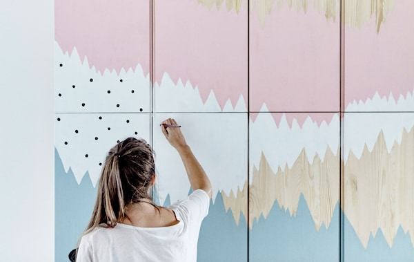 IKEA ideas stylist Therese painting a mural onto IVAR storage