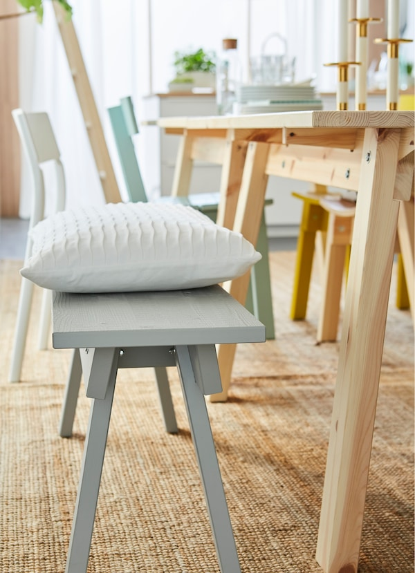 IKEA INDUSTRIELL light grey wood bench by a dining table.