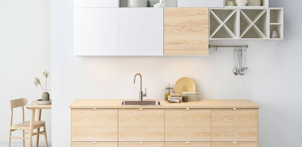 IKEA Kitchen against a white wall, with white and birch cabinets.