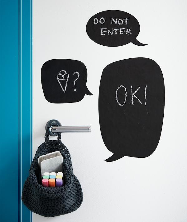 IKEA KLÄTTA Aufkleber Schiefertafel-Motive sind in Sprechblasen- und anderen Formen erhältlich. Auf sie kannst du mit MÅLA Kreiden Nachrichten malen, um weiterhin Ruhe vor den Eltern zu haben. Die Kreide passt wunderbar in NORDRANA Korb in Grau.