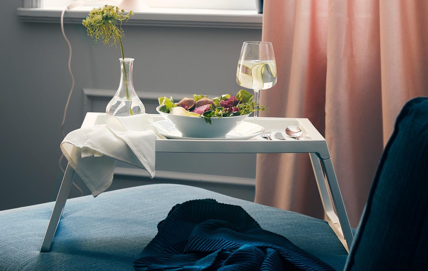 IKEA KLIPSK oherako erretilua sofa baten gainean entsalada-kaiku batekin, edalontzi batekin, ezpainzapi batekin eta lore bat duen pitxer batekin.