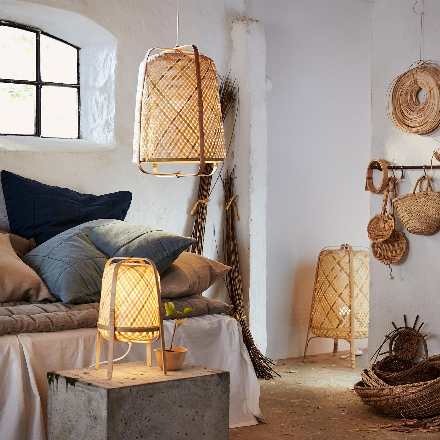 IKEA KNIXHULT Hängeleuchte, Stand- und Tischleuchten in Bambus in einem weissen Raum. Die Leuchten sind geflochten und verfügen aussen über eine geschwungene Form.